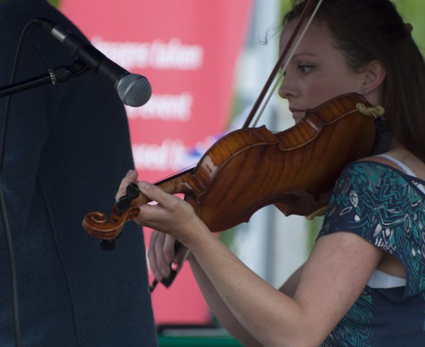 Violinist playing at Burnham Station music festival as part of Station to Station Queen's Celebration